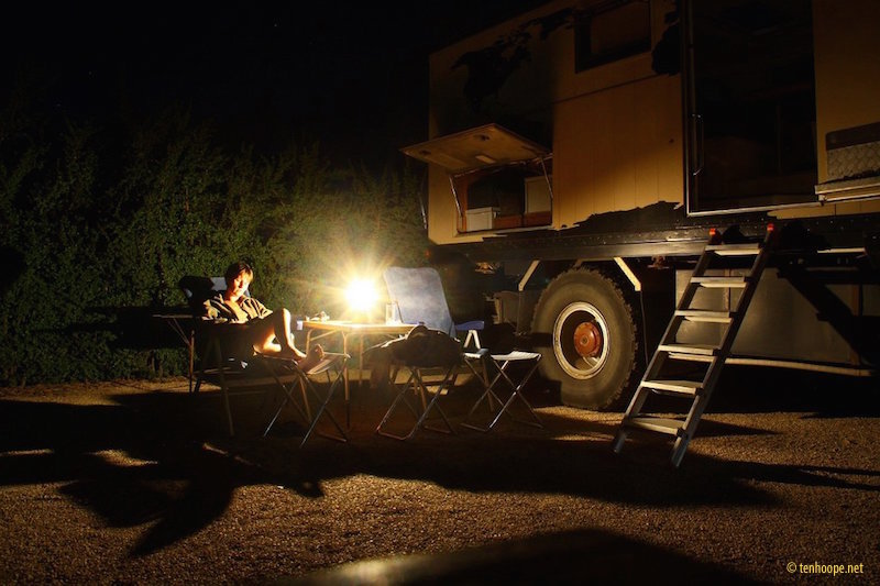 Reading book in the dark next to expedition truck