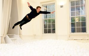 Guy jumping into white ball pit